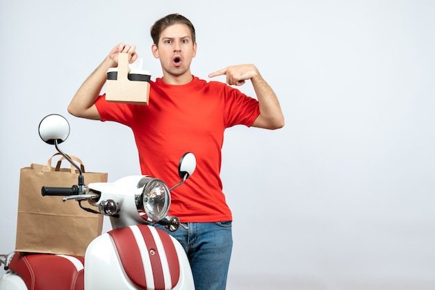 Vista frontale dell'uomo di consegna sorpreso in uniforme rossa che sta vicino all'ordine di puntamento del motorino su priorità bassa bianca