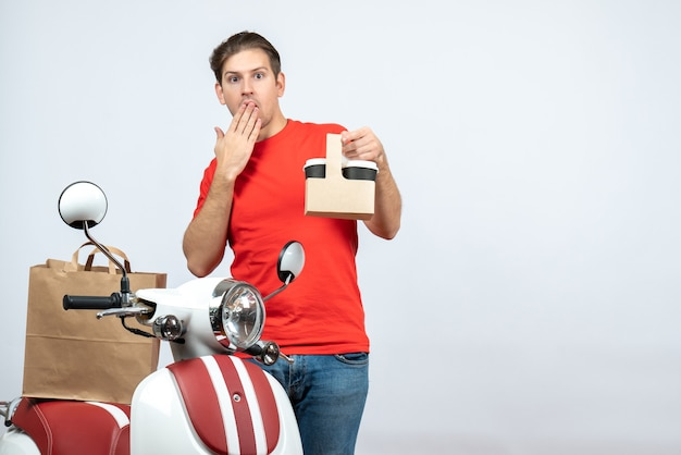 Front view of surprised delivery man in red uniform standing near scooter showing order putting his hand on mouth on white background
