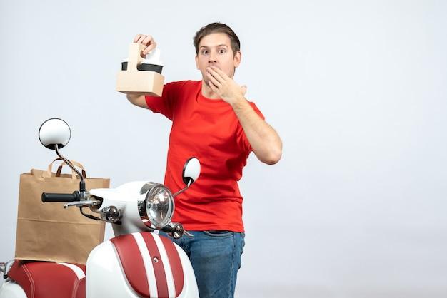 Vista frontale del fattorino sorpreso in uniforme rossa in piedi vicino a scooter che mostra ordine su sfondo bianco