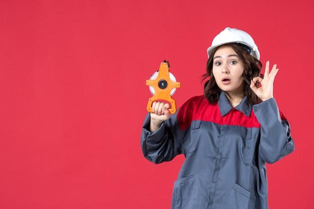Vista frontale dell'architetto donna sorpresa in uniforme con elmetto che tiene il nastro di misurazione e fa il gesto degli occhiali su sfondo rosso isolato