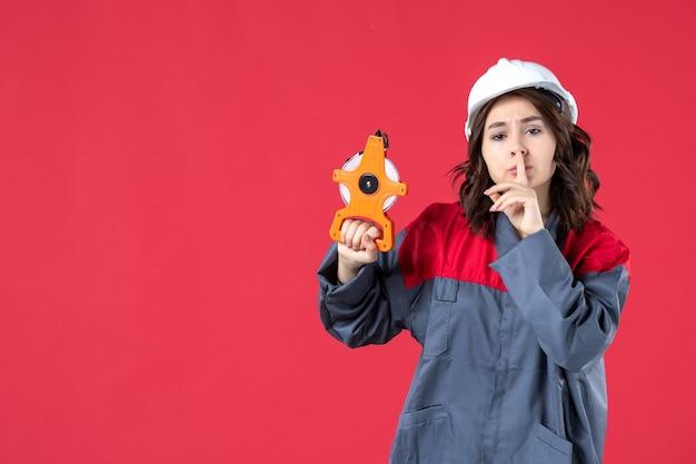 Vista frontale dell'architetto donna sorpresa in uniforme con elmetto che tiene il nastro di misurazione e fa un gesto di silenzio su sfondo rosso isolato