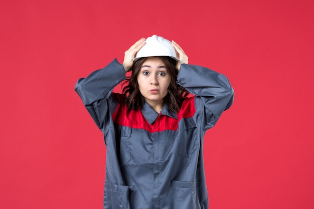 Front view of surprised female builder in uniform with hard hat on isolated red background
