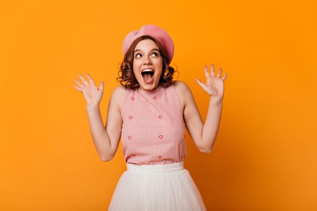 Vista frontale della ragazza francese sorpresa. studio shot di stupita donna elegante in berretto isolato su sfondo giallo.