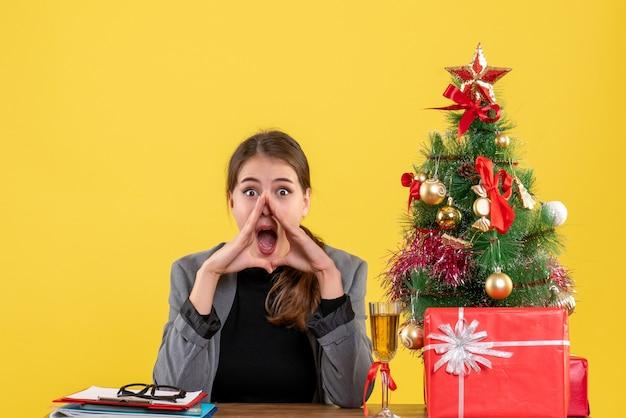 Вид спереди удивленная девушка, сидящая за столом возле елки и подарочный коктейль