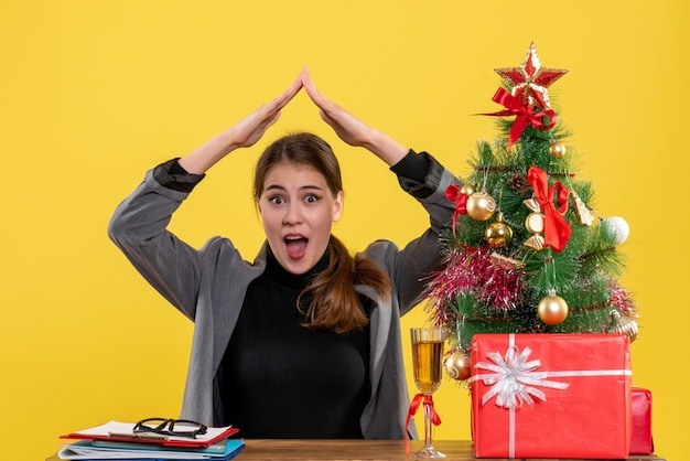 Front view surprised girl sitting at the desk holding hands over head like a roof house near xmas tree and gifts cocktail
