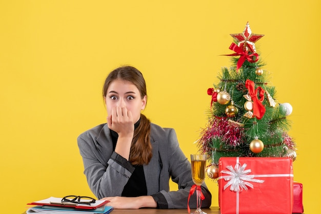 Front view surprised girl sitting at the desk put hand to her mouth xmas tree and gifts cocktail