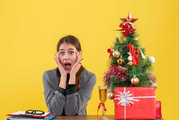 Front view surprised girl sitting at the desk putting hands to her cheek near xmas tree and gifts cocktail