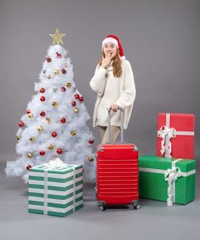 Vista frontale ragazza sorpresa che indossa il cappello della santa in piedi vicino all'albero di natale e regali
