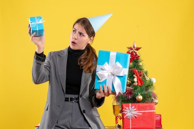Ragazza sorpresa di vista frontale con la protezione del partito che tiene i regali di natale vicino all'albero di natale e al cocktail dei regali