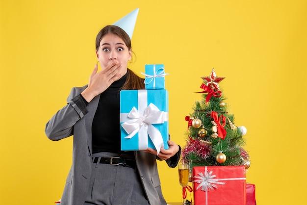 손을 넣어 크리스마스 선물을 들고 파티 모자와 전면보기 놀란 된 소녀