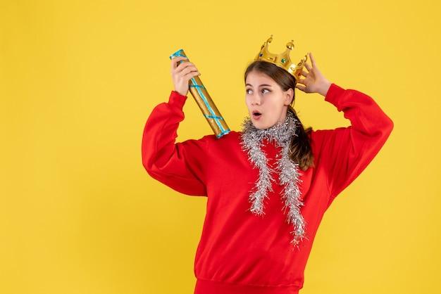 Vista frontale ragazza sorpresa con maglione rosso e corona che tiene il popper del partito