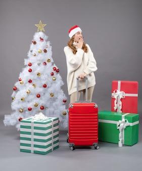 Ragazza sorpresa vista frontale con il cappello della santa che mette la mano al suo mouse che sta vicino all'albero di natale ed ai regali