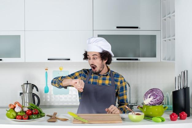Vista frontale dello chef maschio sorpreso con verdure fresche e cucinare con utensili da cucina e controllare il suo tempo nella cucina bianca
