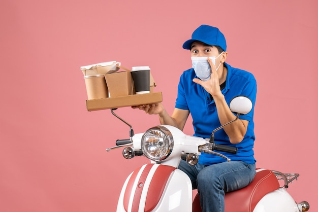 Front view of surprised male delivery person in mask wearing hat sitting on scooter delivering orders calling someone on peach background