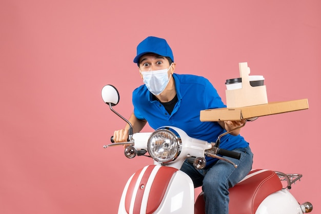 Front view of surprised male delivery person in mask wearing hat sitting on scooter delivering orders on pastel peach background