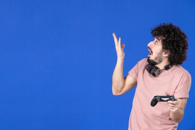正面図は、ゲームパッドの青い背景でビデオゲームをプレイしている男性ゲーマーを驚かせましたティーンサッカー大人の喜びソファ若い勝利仮想ユースプレーヤー