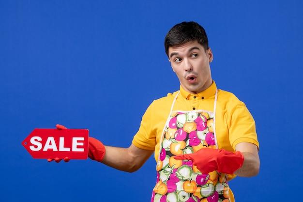 Vista frontale della governante maschio sorpresa in maglietta gialla che tiene il cartello di vendita nella mano destra sulla parete blu