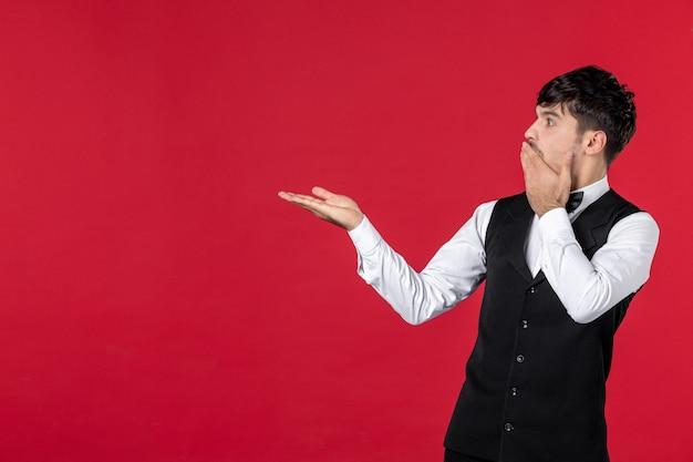 Vista frontale del cameriere maschio sorpreso in uniforme con papillon sul collo e puntando qualcosa sul lato destro sulla parete rossa