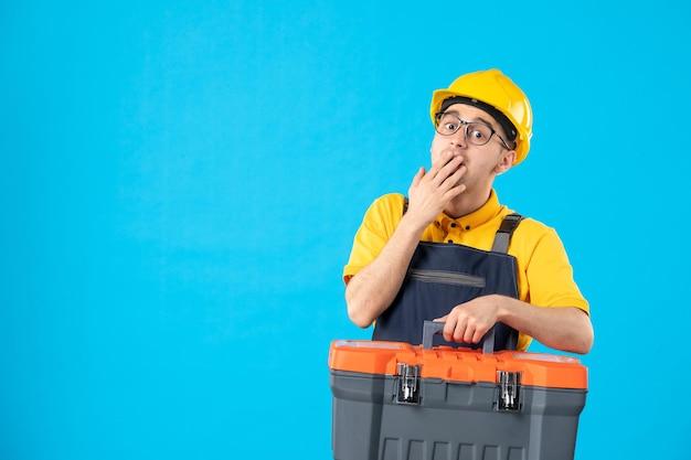 Vista frontale del lavoratore maschio sorpreso in cassetta portautensili di trasporto uniforme gialla sull'azzurro