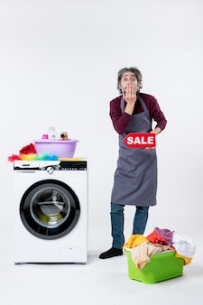 Vista frontale sorpreso l'uomo in grembiule che regge il cartello di vendita in piedi vicino al cesto della biancheria della lavatrice sul muro bianco