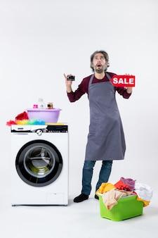 Vista frontale uomo sorpreso che regge la carta e il cartello di vendita in piedi vicino alla lavatrice sul muro bianco