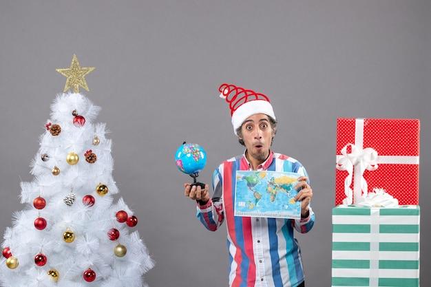 Вид спереди удивленный мужчина держит карту мира и глобус возле рождественской елки и подарочных коробок