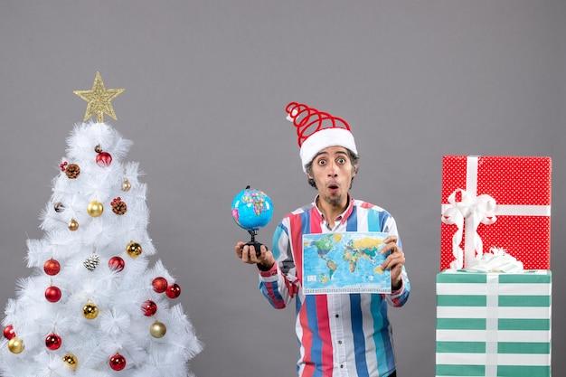 Вид спереди удивленный мужчина, держащий карту мира и глобус, стоящий возле белой елки со звездой