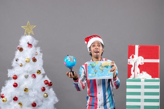 Vista frontale sorpreso l'uomo che tiene la mappa del mondo e il globo