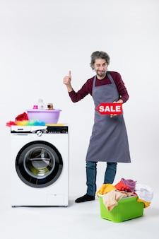 앞치마 앞치마를 입은 남자가 흰 벽에 있는 세탁기 근처에서 엄지손가락을 치켜드는 판매 사인을 들고 놀란 남자