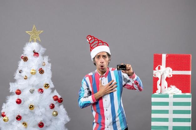 正面図は白いクリスマスツリーの近くに立っている彼の胸に手を入れて驚いた男