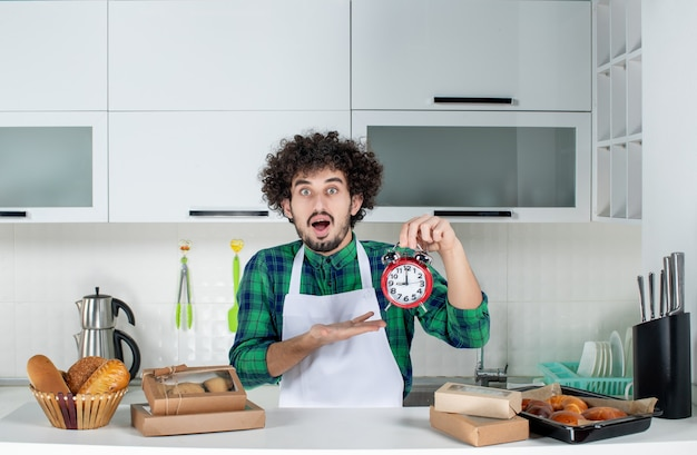Vista frontale dell'uomo sorpreso in piedi dietro il tavolo con vari pasticcini e che punta l'orologio nella cucina bianca