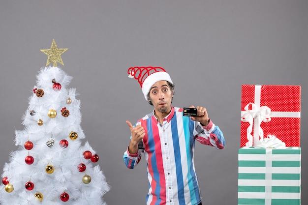 다른 선물 근처에 서있는 크리스마스 트리를 보여주는 신용 카드로 전면보기 놀란 남자