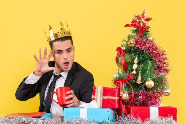 Вид спереди удивлен человек с короной, глядя на чашку возле рождественской елки и подарков