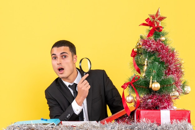 Vista frontale uomo sorpreso con lupa ottica in mano seduto al tavolo albero di natale e regali