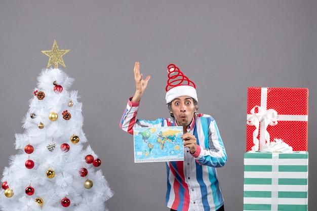 Вид спереди удивил человека в новогодней шапке со спиральной пружиной и полосатой рубашке, держащей карту, подняв руку