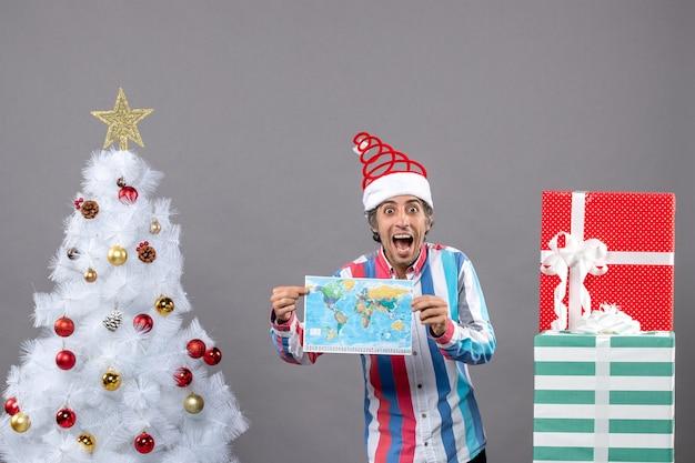 Vista frontale uomo sorpreso con molla a spirale cappello santa azienda mappa vicino albero di natale bianco e presenta con copia spazio