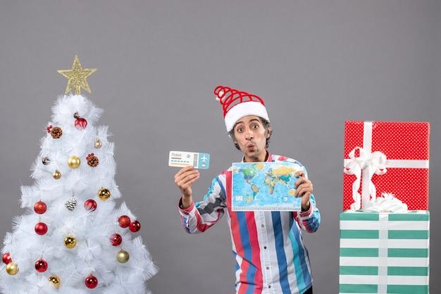 나선형 봄 산타 모자 세계지도 및 여행 티켓을 들고 전면보기 놀란 남자