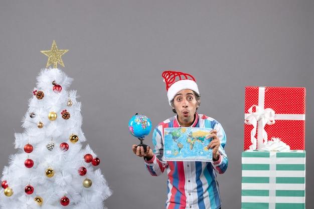 Vista frontale uomo sorpreso con molla a spirale santa hat holding mappamondo e globo