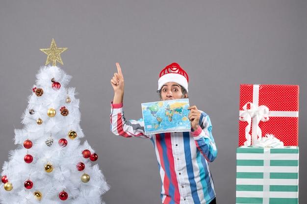 나선형 봄 산타 모자 높은 곳에서 가리키는 세계지도를 들고 전면보기 놀란 남자