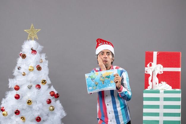 나선형 봄 산타 모자는 그의 얼굴에 손을 넣어 세계지도를 들고 전면보기 놀란 남자