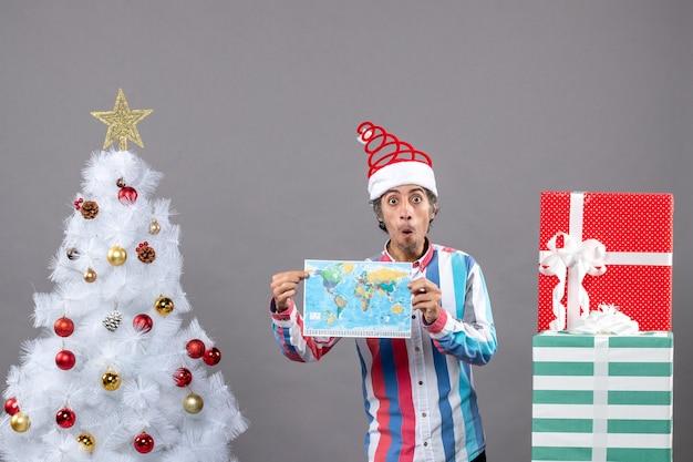 Vista frontale uomo sorpreso con la molla a spirale del cappello della santa e la camicia a strisce che tiene la mappa vicino all'albero di natale bianco e presenta con lo spazio della copia