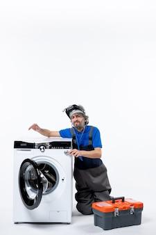 Vista frontale del riparatore sorpreso che mette lo stetoscopio sulla borsa degli attrezzi della lavatrice sulla parete bianca