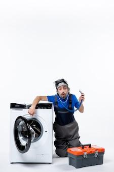 Vista frontale del riparatore sorpreso seduto vicino alla borsa degli attrezzi della lavatrice sul muro bianco