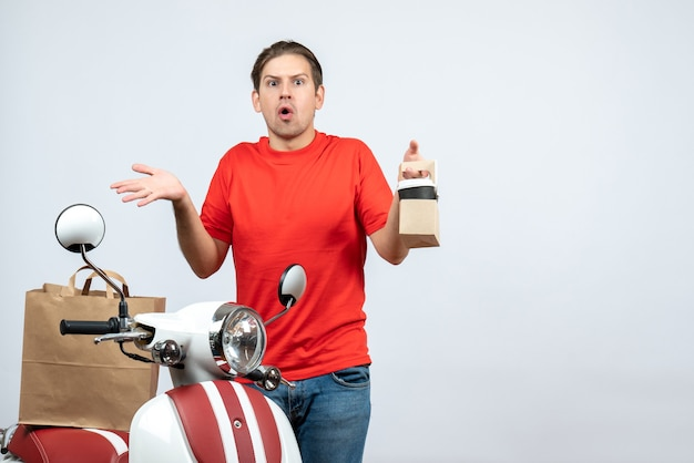Vista frontale dell'uomo di consegna scioccato sorpreso in uniforme rossa che sta vicino al motorino che mostra ordine su fondo bianco