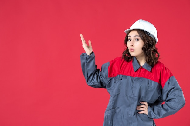 Front view of surprised shocked female builder in uniform with hard hat and pointing up on isolated red background