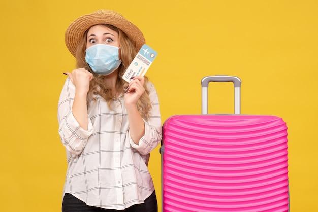 Vista frontale della ragazza in viaggio sorpresa che indossa la maschera che mostra il biglietto e in piedi vicino alla sua borsa rosa su giallo