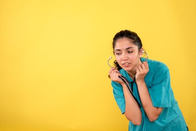 正面図黄色の背景に聴診器を保持している制服を着た女性医師を驚かせた