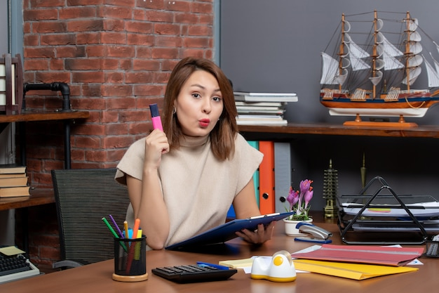Vista frontale donna sorpresa che tiene in mano un evidenziatore seduto in ufficio