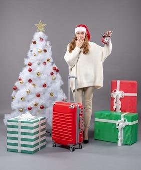 正面図は、クリスマスツリーの近くに立っている赤い目覚まし時計を示す驚いたクリスマスの女の子
