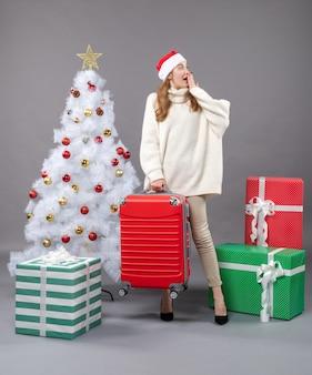 彼女の赤い旅行バッグを保持しているサンタの帽子をかぶった正面図は驚いたクリスマスの女の子